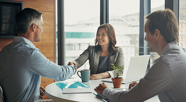 Business people meeting and shaking hands at a table stock photo
